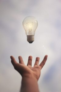 light bulb floating above a hand. idea in motion